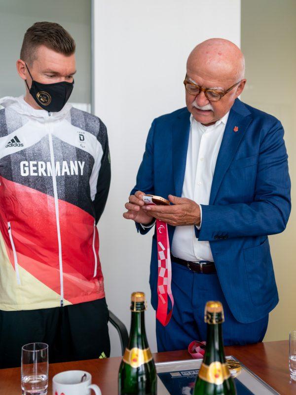 """Gerd Schmelzer, Geschäftsführer von Lebkuchen Schmidt und der alpha Gruppe nimmt die Bronzemedaille von Matthias Schindler """"unter die Lupe"""" (Foto: DC-Fotografie.de)"""